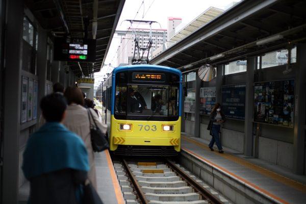 南海高野線住吉東駅のホームから、黄色と青色の2色に塗装された電車が出発しようとしている風景。