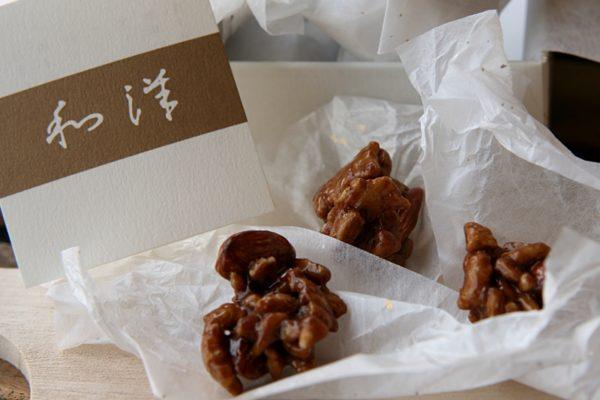 和洋の個包装を開いた様子。アーモンドが一口大に固められており、深い茶色で光沢がある。