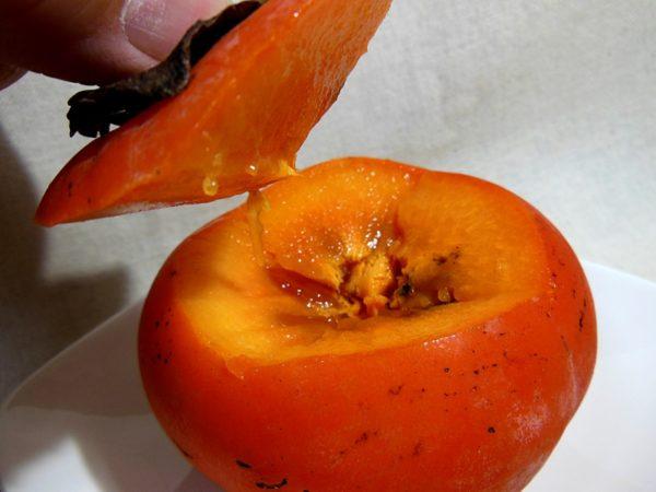柿のヘタを蓋のようにして切り取り、持ち上げている様子。凍った柿の中身が見えている。