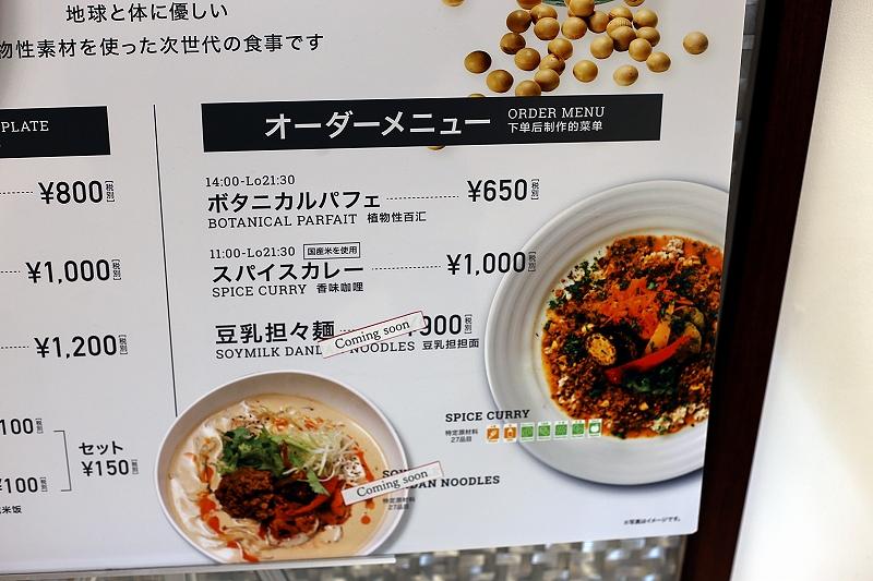 メニュー看板にあるオーダーメニュー「豆乳担々麺」の文字の上に「comming soon」のシールが貼られている様子