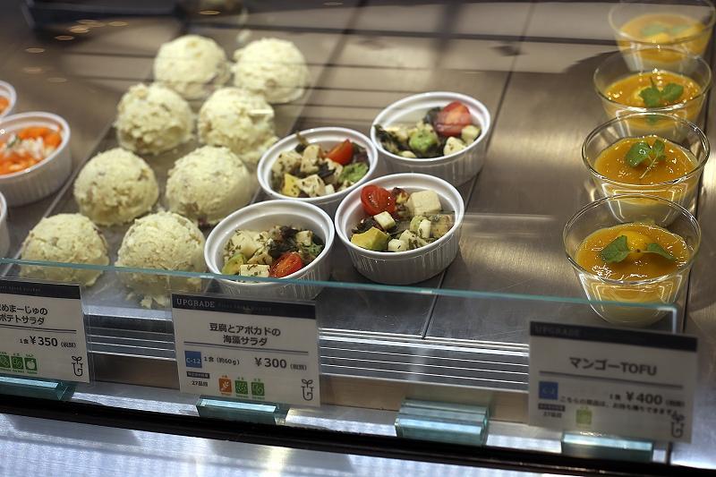 ショーケースに並んだポテトサラダや豆腐とアボカドの海藻サラダ、マンゴーのジェルがのったマンゴーTOFU