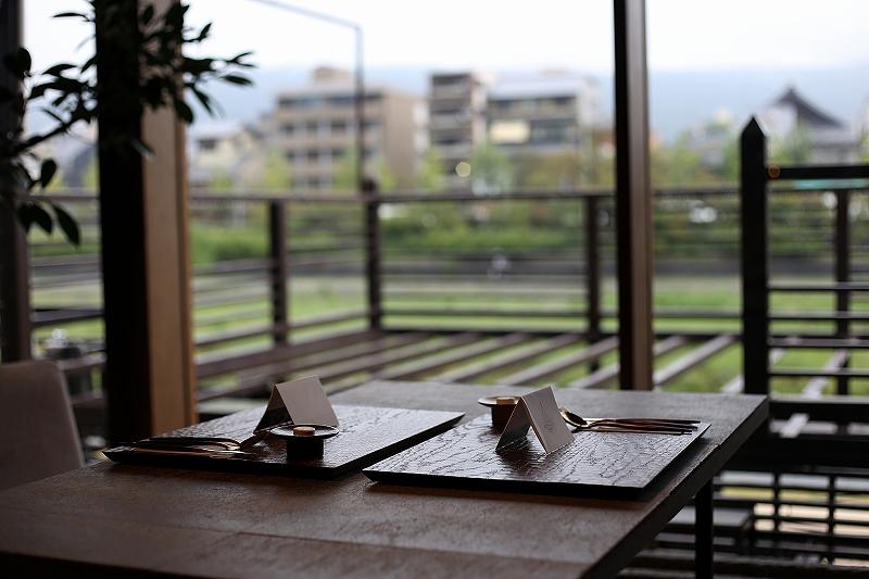 木製テーブルの上に2名分のカトラリーと席札が置かれているレストランの一角の写真
