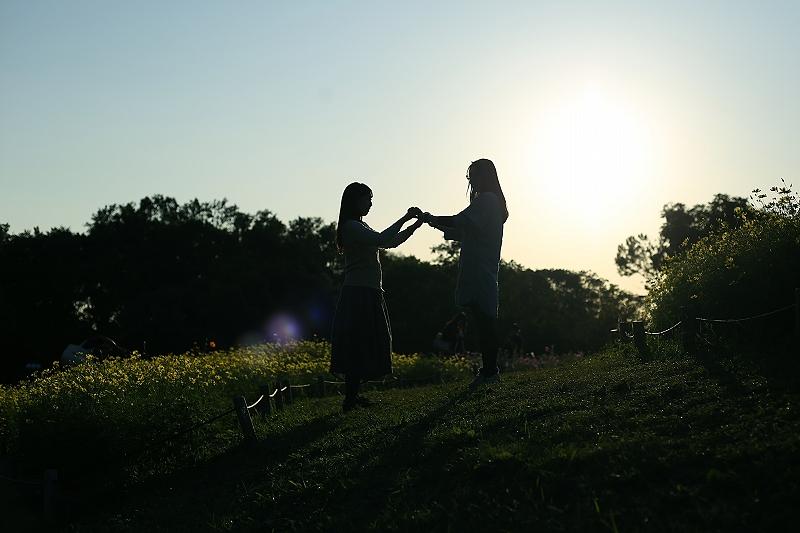 丘の上で女性2人が向かい合って両手を取り合っている写真