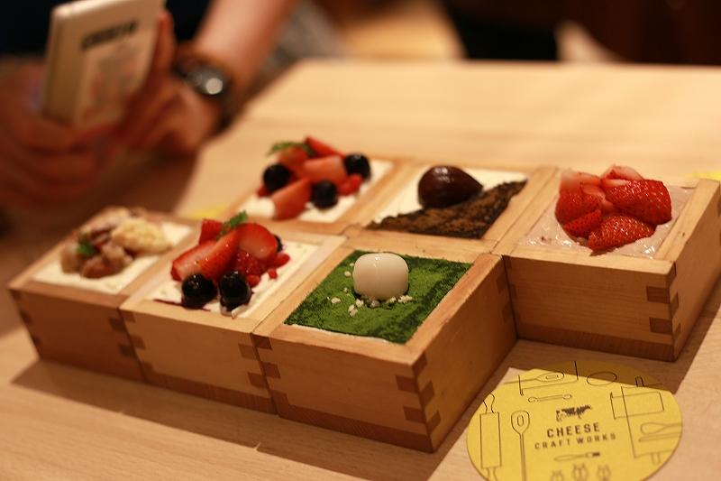 枡に入った、フルーツや抹茶、チョコレートがのった数種類のチーズケーキの写真