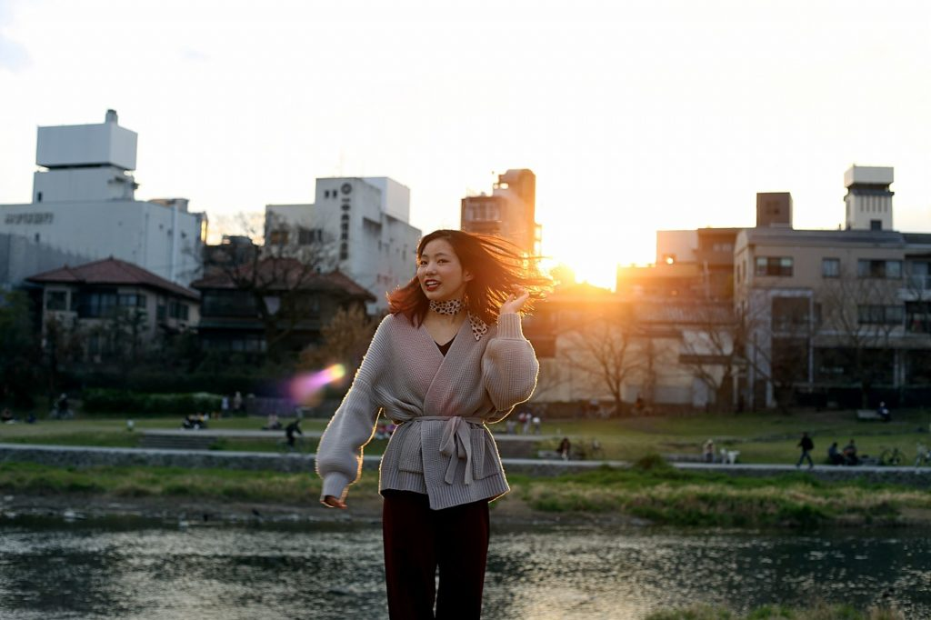 川の土手で夕日に髪をなびかせる女性の写真