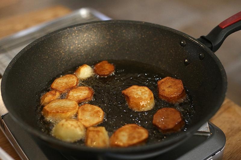 油を引いたフライパンでカットしたじゃがいもを揚げ焼きにしている写真