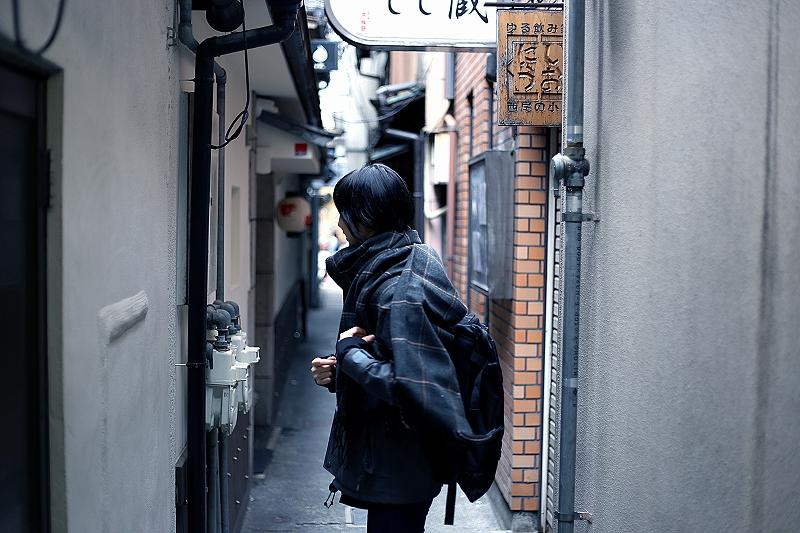 狭い路地に人が佇んでいる写真