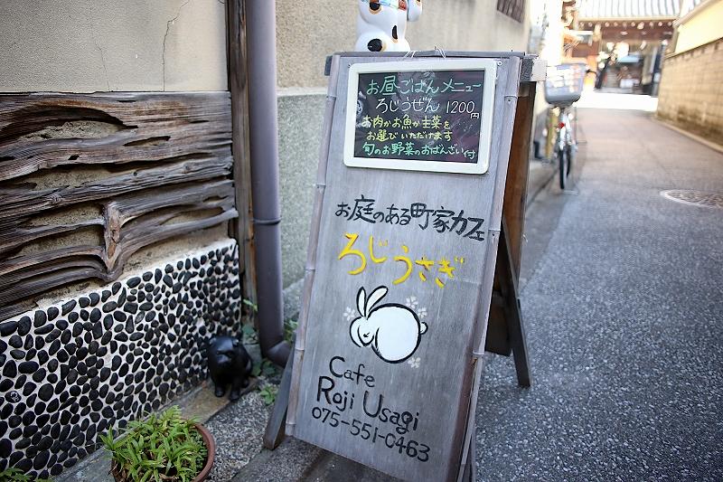 「お庭のある町家カフェ ろじうさぎ cafe Roji Usagi 075-551-0463」と書かれた看板。お昼ごはんメニューの黒板がかけられており、「ろじうぜん 1200円 お肉かお魚か主催をお選びいただけます 旬のお野菜のおばんざい付」と手書きされている。
