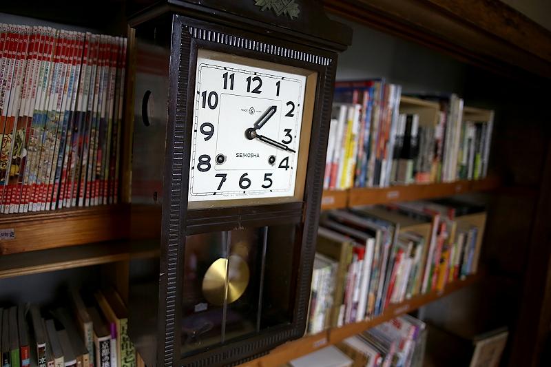 本棚に取り付けられた、黒くて四角い小さな振り子時計