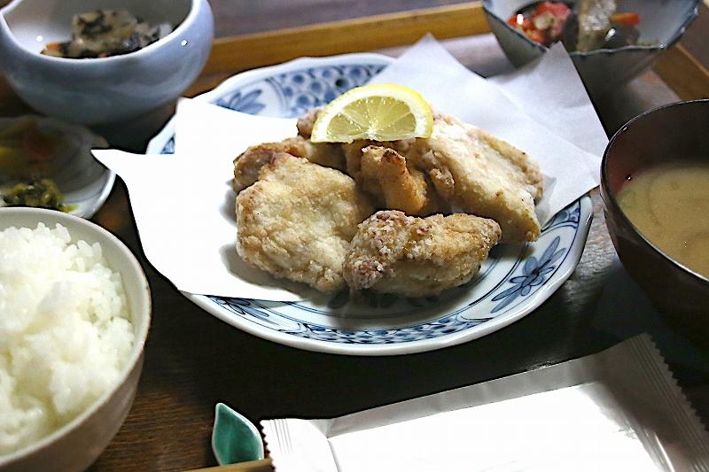 青い模様の入ったお皿に盛り付けられたから揚げ。上に半月型にスライスされたレモンが添えられている。
