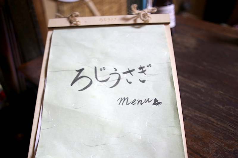 薄緑色の和紙に手書きで「ろじうさぎ menu」と書かれている、ボードに挟まれたメニューの表紙