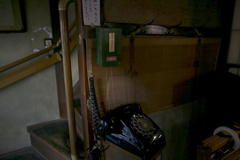 黒電話のオブジェ。壁に使用料を入れる緑色の小箱が取り付けられている。