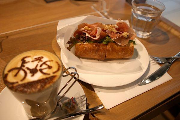 フランスパンに生ハム、クリームチーズ、レタスが挟まれたサンドイッチと、自転車のラテアートが施されたカフェラテ