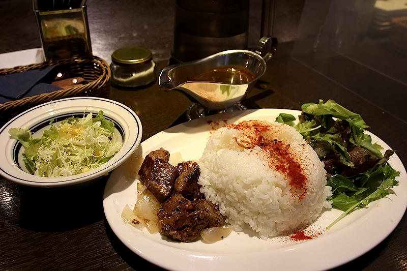 丸く盛り付けられたライスにステーキと葉野菜が添えられたプレートと、クレービーボートに入ったカレー、別盛りの千切りキャベツとコーンのサラダ