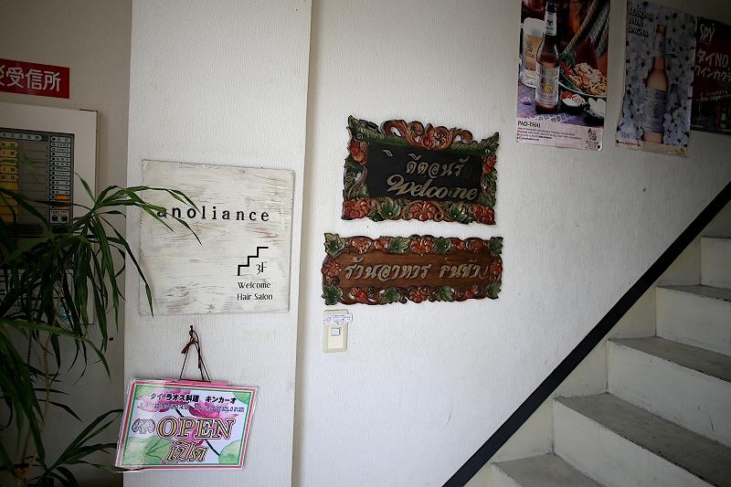 ビル内の階段の横に welcome と書かれた看板と、タイ語で書かれた看板が壁にかけられている様子