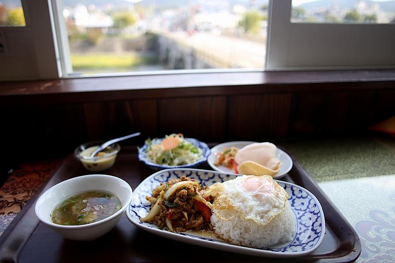目玉焼きの乗ったガパオライスのお皿と、スープ、サラダ、えびせんべいの小皿とデザートの小鉢
