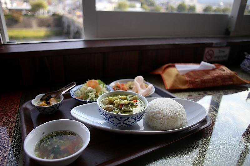 丸く盛り付けられたライスの横にグリーンカレーが入ったお椀が乗ったお皿と、スープ、サラダ、えびせんべいの小皿とデザートの小鉢