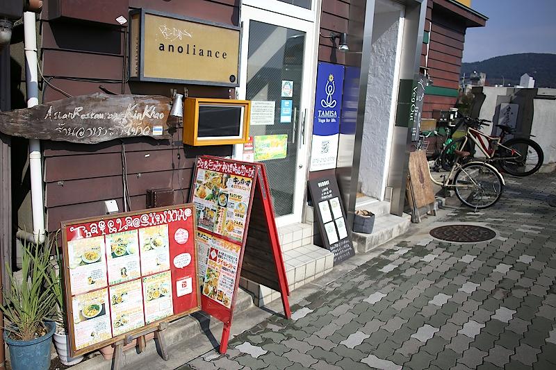 キンカーオが入っている建物の入口。ビルの扉横にタイ語と日本語で書かれたキンカーオのメニュー看板が建てられている。